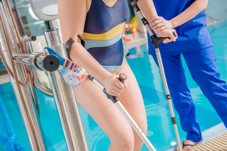 Children Pool Rehabilitation. Practitioner Physician Helping Disabled Girl To Reach the Swimming Pool By Special Chair Lift. Caucasian Disabled Girl. Physical Therapy Concept Photo.