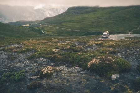 RV Trip in Scandinavia. Wild Norway Mountains Landscape and the Camper Van on the Road. Stock Photo