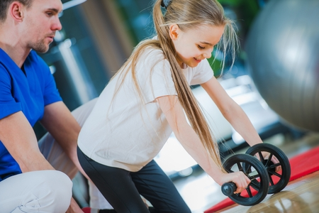 medical practitioner: Little Girl Exercise with Medical Practitioner. Stock Photo