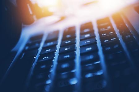 現代のラップトップ コンピューター ワークステーションのクローズ アップ写真。赤みを帯びた光源を暗い青のグラデーション。