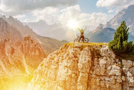 Extreme Bike Trail Mission Accomplished op de top van de berg. Biker met zijn fiets in de lucht als teken van overwinning.