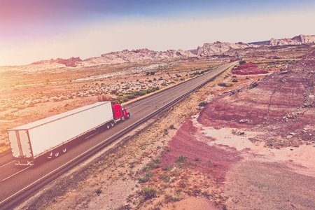 Truck Transport Concept. Semi Truck on the American Desert Highway. Stock Photo