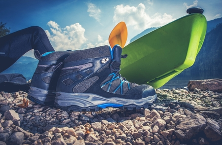 sport shoe: Outdoor Recreation Objects. Good Outdoor Hiking Shoes, Kayak and the Camping on the Edge of the Lake.