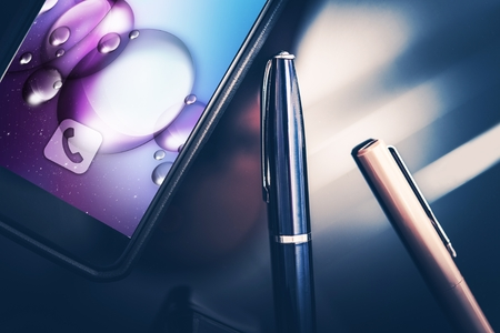 business equipment: Smartphone in Business. Modern Desk Equipment and Tools. Smartphone and Elegant Pens on the Glassy CEO Desk. Closeup Photo.