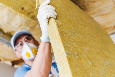 construction material: Caucasian Construction Worker with Piece of Insulating Material, Roof Insulating by Mineral Wool. Stock Photo