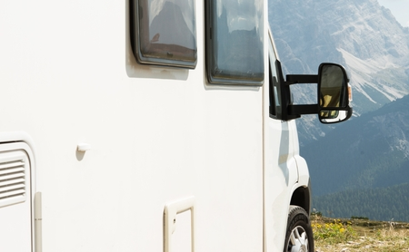 RV Camper Scenic Camping in the Mountains Wilderness. Motorhome Closeup. Stock Photo
