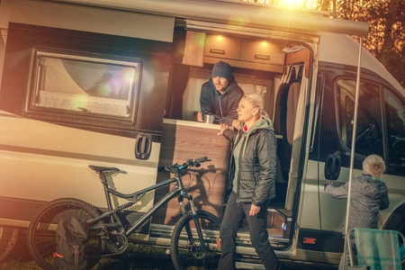motorcoach: Family Motorhome Camping. Young Modern Caucasian Family with RV Motorhome Camper Van on the Campsite. Stock Photo