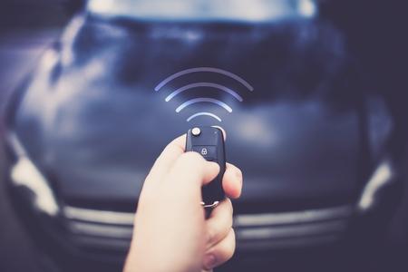 Alarme voiture automatique et à distance de verrouillage central. Clés de voiture à la main du pilote d'envoyer le signal au véhicule. Banque d'images - 76269700
