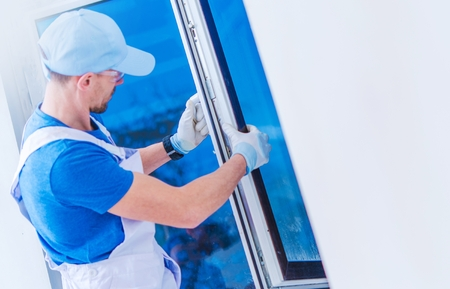 Window Replacement Installation by Professional Caucasian Construction Worker. Home Building or Remodeling Photo Concept. 스톡 콘텐츠