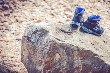 Drying Trekking Shoes on the Large Stone. Trail Hiking Concept Photo.
