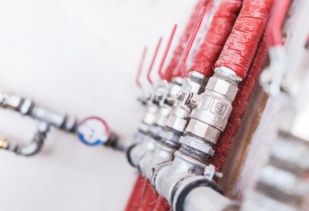 Système de plomberie à domicile Photo Gros plan. Tuyaux isolés rouges avec robinets à tournant sphérique. Système d'approvisionnement en eau résidentiel.