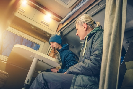 motorcoach: Young Couples in RV Camper Preparing For the Next Day of Drive Taking Look on the Local Map. Stock Photo
