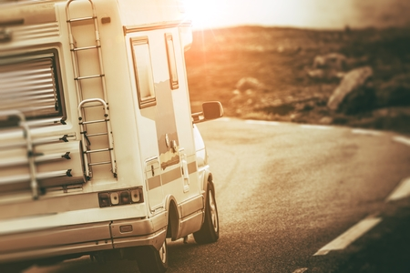 Camper Van on the Scenic Mountain Road. RV Motorhome Traveling Concept. Sepia Color Grading.