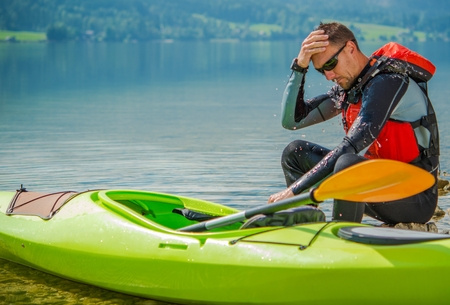 Resting Kayaker on the Rocky Lake Shore. Young Caucasian Kayaker with His Kayak. Stock Photo