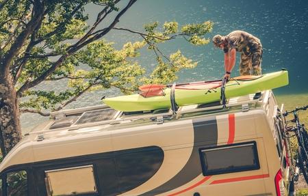 motorcoach: Men Installing Kayak on the RV Camper Van. Preparing For the Next Motorhome Trip.