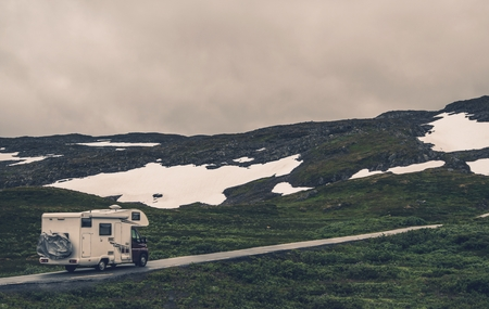 motorcoach: Camper Van and Rainy Weather During Spring Trip in Norway. Motorhome RV on the Mountain Road.