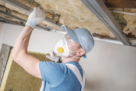 Wool Home Insulating. Caucasian Home Renovation Worker with Mineral Wool. Stockfoto