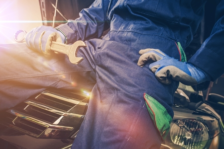 Car Mechanic with Wrench in Hand Seating on the Front of the Vehicle with Open Car Hood. Preparing For Work.