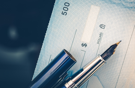 paying: Check Issuing Concept Closeup Photo. Business Check and the Elegant Fountain Pen. Executive Desk.
