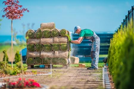 Préparation à l'installation d'herbe naturelle à l'intérieur du jardin de l'arrière-cour. Thème de conception et de construction de jardins. Pile de Grass Turfs.