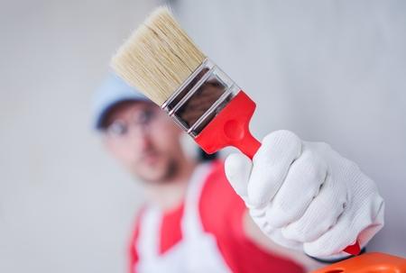 paint tool: Paintbrush Painting Job. Caucasian Room Painter Showing His Brand New Paintbrush. Stock Photo