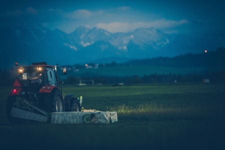 Grass Mowing on the Farm During Late Evening Hours. Lesser Poland. Industrial Heavy Duty Grass Mower Installed on a Tractor.
