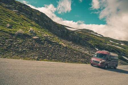 Recreation Vehicle RV Travel. Modern Burgundy Camper Van on the Scenic Mountain Road.
