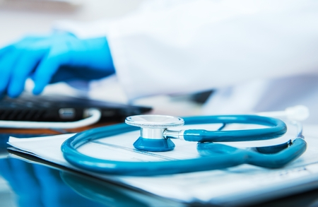 Closeup on a Stethoscope Lying on the Doctors Desk. Stock Photo