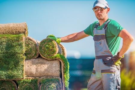 Natural Grass Turfs Installer. Caucasian Gardening Industry Worker. Installation of Brand New Grass. Stock Photo