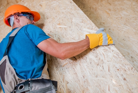 Worker Moving Plywood Boards Within Residential Construction Site. Home Building. Stock Photo