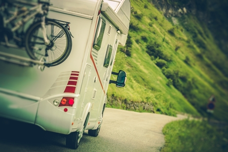 Camper Van on the Road. Class C Motorhome Coach with Bikes on the Rear Side Bike Rack. Family RV Travel.