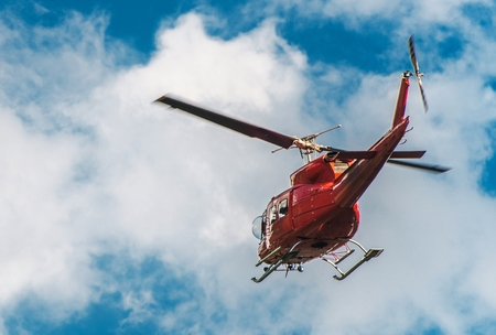 Red Helicopter Logging in the Air. Heli-Logging Transportation. 版權商用圖片