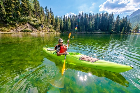 Shallow Scenic Lake Kayak Tour. Kayaker caucásico en el lago Misurina en Italia septentrional. Dolomitas italianos. Foto de archivo - 83733480