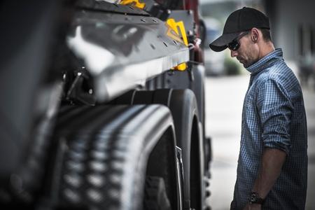 Vérification de la charge du conducteur de camion. Conducteur de camion semi-caucasien vérifiant son véhicule et la charge.