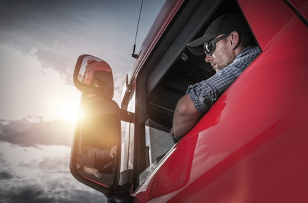 Red Semi Truck. Caucasian Truck Driver Preparing For the Next Destination. Banque d'images
