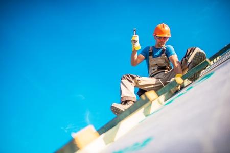 Trabajos De Construcción De Techos Casa. Trabajador del Cáucaso en su 30s en el nuevo edificio de techo. Trabajos de martillo. Foto de archivo