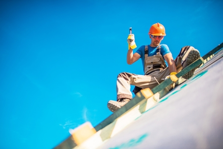 House Roof Construction Works. Caucasian Worker in His 30s on the New Building Roof. Hammer Works.