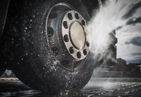 Semi Truck Wheels High Pressured Water Washing Closeup Photo. Stock Photo