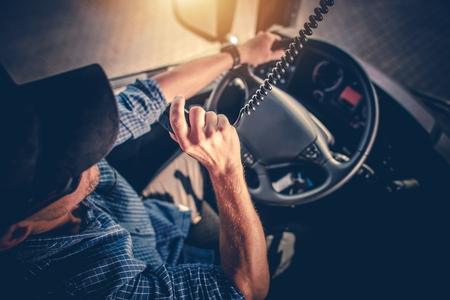 Semi Truck Driver Making Conversation with Other Truck Drivers Through CB Radio. Standard-Bild