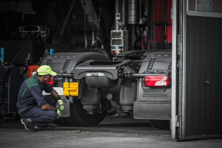 Truck Service Technician Job. Kaukasische Vrachtwagen Werktuigkundige die op Semi Vrachtwagentractor controleert.