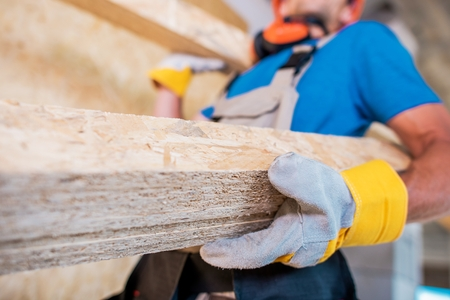 Worker with Wooden Materials in Hands. Closeup Photo. Construction Site.