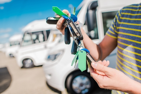 RV Camper Vans and Motorhomes Salesperson with Keys To  Vehicles on the Dealer Lot.