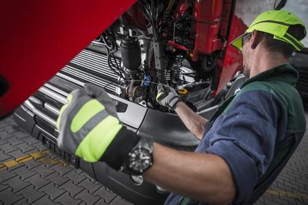 백인 서비스 기술자에 의한 트럭 서비스 오일 레벨 점검. 세미 트럭 정비.
