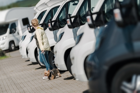 motorcoach: Caucasian Woman Buying New Camper Van. Looking Around To Find the Perfect Camper on the Dealership Lot.