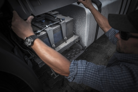 Checking on Truck Battery. Trucking Concept Photo. Caucasian Truck Driver Opening Vehicle Battery Compartment. Banco de Imagens - 85263442