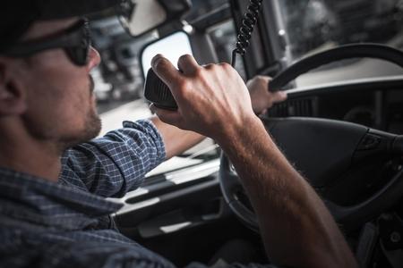 백인 세미 트럭 운전사는 호송에서 다른 트럭 운전사와 CB 라디오에 말하기.