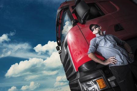 Proud Trucker and His Truck. Caucasian Trucker with Euro Semi Tractor Closeup Photo