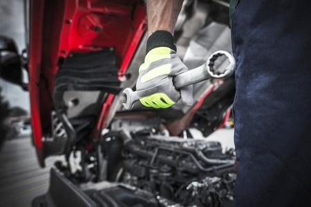 세미 트럭 정비공 작업을 준비합니다. 정비공 손에 대형 스테인레스 스틸 렌치입니다.