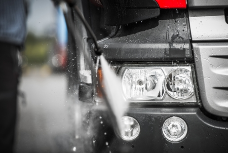 Manual Truck Washing Using High Pressured Hot Water with Detergents. Closeup Photo. Banque d'images