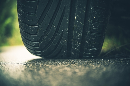 Modern Car Tire on the Road Closeup Photo. Summer Season Pneumatic Tire on a Paved Road.  Stock Photo